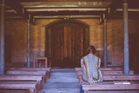 woman exercising faith at church