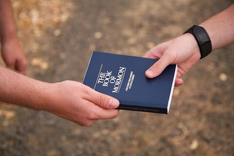 Person Handing Book of Mormon