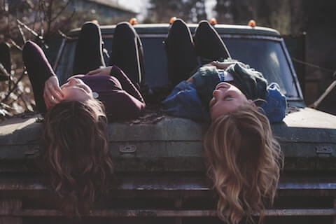 Friends talking on top of a car