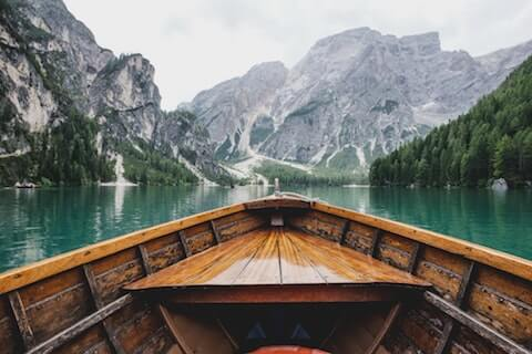 Nature scene showing boat on water surrounded by mountains