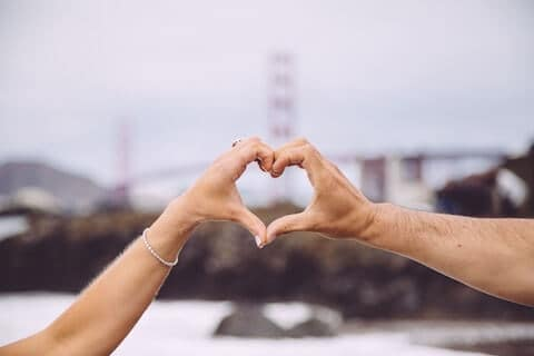 Male and female hand making a heart symbol