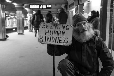 "Homeless man holding sign that says ""Seeking human kindness"""